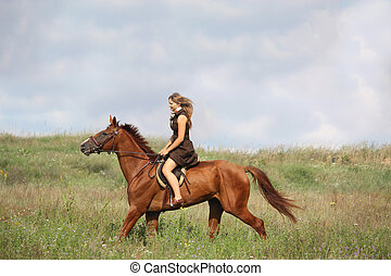 Beautiful teenage girl riding horse at the field in summer
