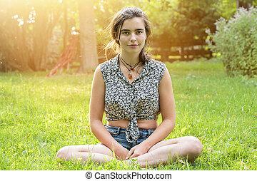 beautiful teenage girl sitting on a meadow