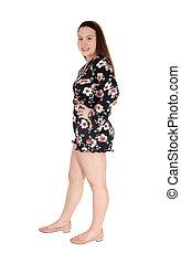 Beautiful teenage girl standing in shorts in profile