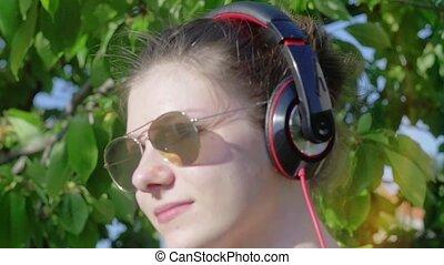 Beautiful teenage girl with headphones enjoys music