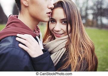 Beautiful teenage girl with her boyfriend in park