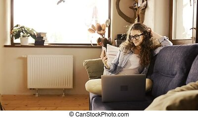 Beautiful teenage girl with smartphone sitting on couch,...