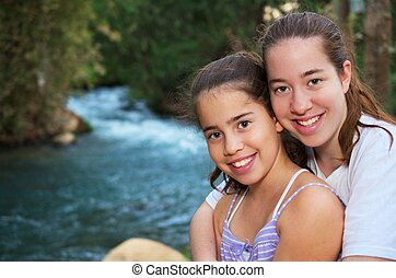 Beautiful teenage sisters relaxing on the Jordan River