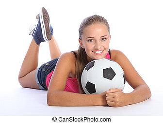 Beautiful teenage soccer girl lying on floor