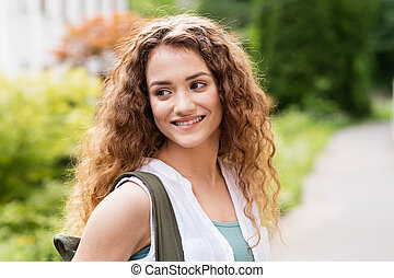 Beautiful teenage student posing outdoors in park.