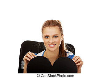 Beautiful teenage woman holding paper heart