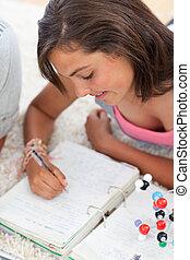 Beautiful teenager doing homework on the floor