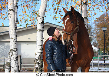 Beautiful teenager girl and bay horse portrait in autumn