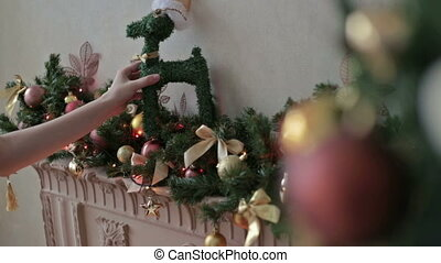 Beautiful teenager girl decorating fireplace