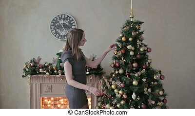 Beautiful teenager girl decorating the Christmas tree