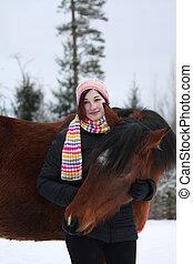 Beautiful teenager girl hugging brown horse in winter