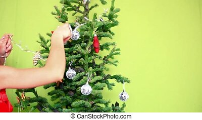 Beautiful teenager girl in Winter Hat decorating the Christmas tree on a green background