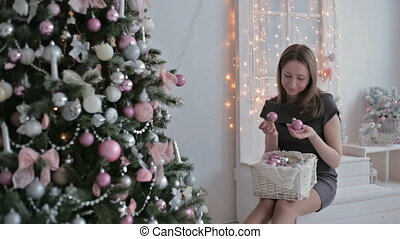 Beautiful teenager girl sorting out christmas balls and decorating the Christmas tree