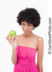 Beautiful teenager holding a green apple while looking at the camera