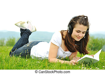 Beautiful teenager reading a book in nature