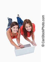 Beautiful teenagers lying down with a laptop while looking at the camera