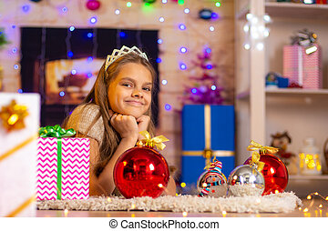 Beautiful ten-year-old girl lies on a rug in the New Year?s interior and looks at the frame cheerfully