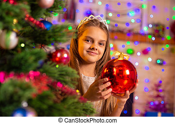 Beautiful ten year old girl peeking out with a big red ball from behind a Christmas tree