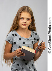 Beautiful ten year old girl reads a book and looks into the frame