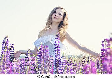 Beautiful tender woman in a field of flowers