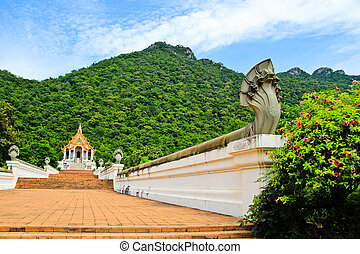 Beautiful thai church in front of the mountain against blue sky background