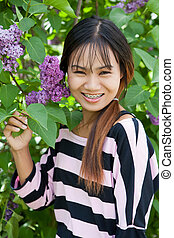 Beautiful Thai woman with braces in the park, shallow dof