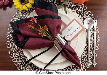 Beautiful Thanksgiving table setting with lace doily place setting and fine bone chia with vintage silverware, red and black napkins on dark mahogany wood table with autumn pumpkin, grapes and sunflower decorations.
