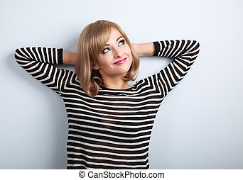 Beautiful thinking blond young woman in sweater looking up on blue background