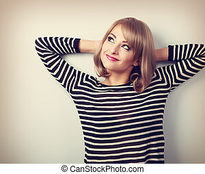 Beautiful thinking blond young woman in sweater looking up. Toned portrait