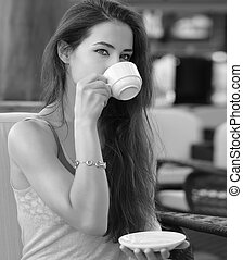 Beautiful thinking girl drinking coffee in cafe. Black and white portrait