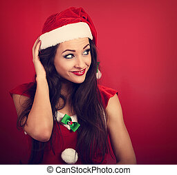 Beautiful thinking grimacing woman in santa claus christmas costume scratching the head on red background with empty copy space. Closeup portrait