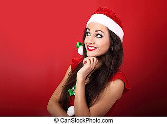 Beautiful thinking smiling woman in santa claus christmas...
