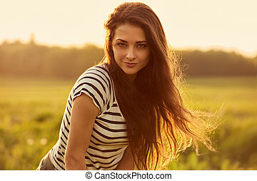 Beautiful thinking smiling young woman looking happy with long bright hair on nature sunset summer background. Closeup
