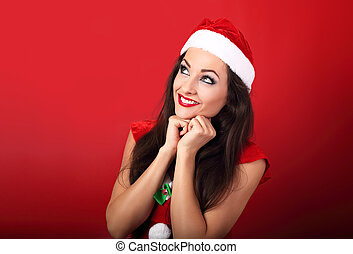Beautiful thinking woman in santa claus christmas costume looking up on red background with empty copy space