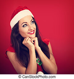 Beautiful thinking woman in santa claus christmas costume looking up on red background with empty copy space. Closeup portrait