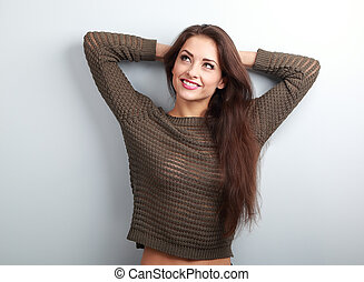 Beautiful thinking woman in sweater looking up