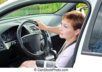 Beautiful thinking woman inside the sport car behind the wheel looking