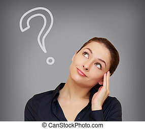 Beautiful thinking woman with question mark looking up on grey