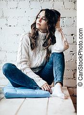 Beautiful thoughtful woman relaxing on brick wall background
