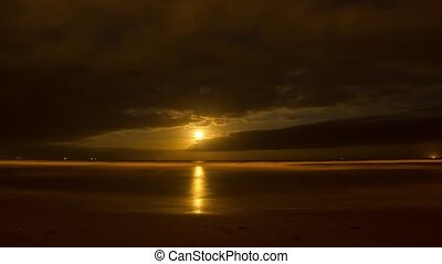 Beautiful timelapse of the moon rising on the sea at night with its beautiful reflections