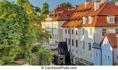 beautiful timelapse view of a street with old water mill in a canal in center of Prague