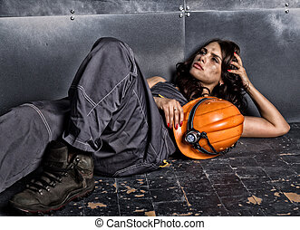 Beautiful tired sexy miner worker in orange helmet with flashlight lies on a floor on steel background