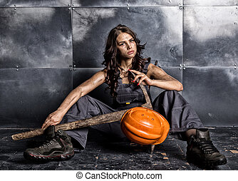 Beautiful tired sexy miner worker in orange helmet with flashlight sitting on a floor on steel background. woman holding pickaxe