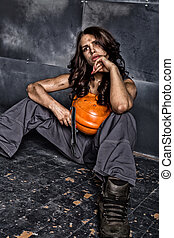 Beautiful tired sexy miner worker in orange helmet with flashlight sitting on a floor on steel background