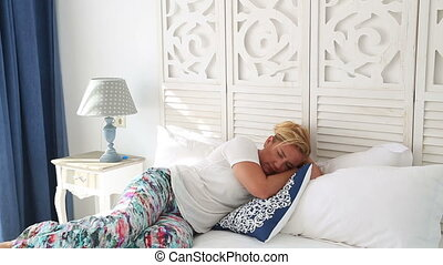 Beautiful tired woman sleeping on bed