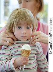 Beautiful toddler eating ice cream, mother care