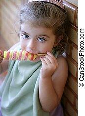 Beautiful toddler girl eating a  ice cream