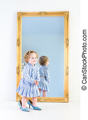 Beautiful toddler girl with curly hair wearing a blue dress stan