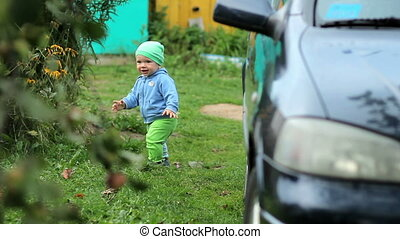 Beautiful toddler walking in the garden near the house. Nearby is a dark car and apples grow. Kid in hat and jacket