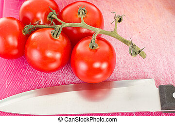 Beautiful tomatoes with kitchen knife on chopping board